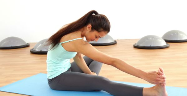 stock-footage-fit-brunette-stretching-on-exercise-mat-at-the-gym