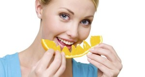 smiling woman eats the fresh orange
