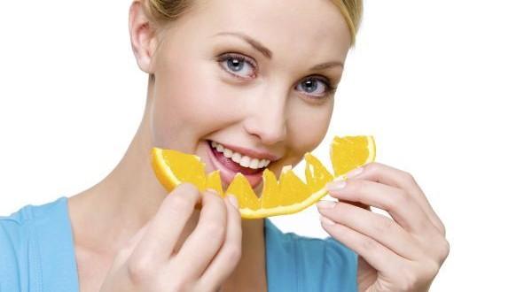 smiling woman eats the fresh orange