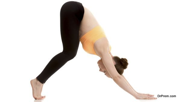 Beginner yoga girl stretching in easy variation of downward-facing dog pose, adho mukha svanasana on white background with bent knees, preparation for asana