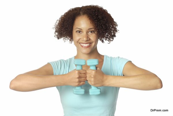 Athletic, healthy, smiling young woman lifting small weights