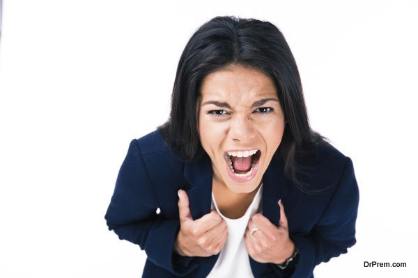 Angry businesswoman screaming over white background and looking at camera