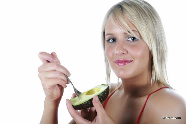 Pretty blonde girl holding and eating a avocado
