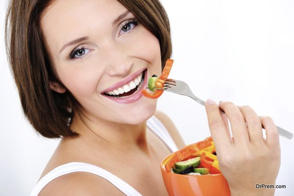 Portrait of a happy attractive young woman eats vegetable salad