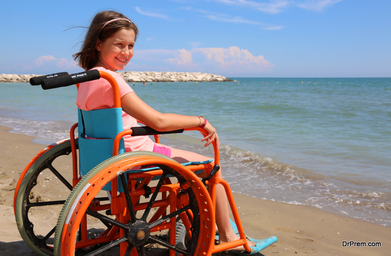 Pretty little girl in the wheelchair by the sea