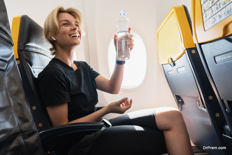 woman drinks water during her flight